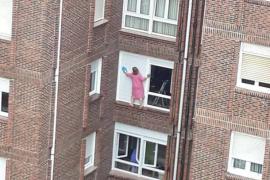 Mujer limpia las persianas de un cuarto piso en una arriesgada maniobra.