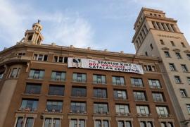 Los activistas vuelven a estirar la pancarta contra el Rey en la plaza de Cataluña