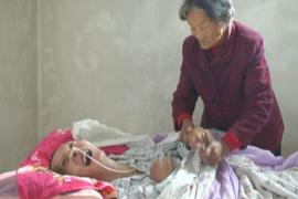 La madre cuidando a su hijo en coma
