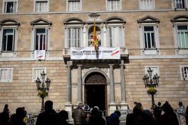 El edificio de la Generalitat con pancarta con lazo blanco y franja roja por presos políticos