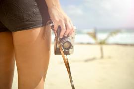 Chica con cámara en la playa