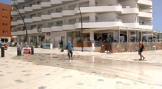 Un trabajador del paseo de ses Figueretes vierte residuos en la playa