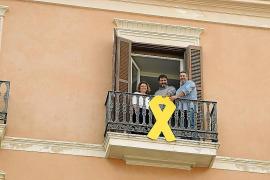 Cargos de Més posan tras el lazo amarillo de su balcón