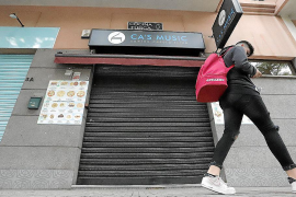 Un joven pasa por delante de la barrera del restaurante Ca's Músic de Palma